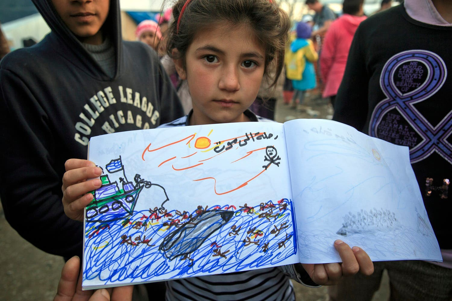 Shaharzad Hassan, 8 year-old from the Syrian city of Aleppo poses with a drawing she made, depicting a migrants rescue operation by the Greek navy, at the northern Greek border station of Idomeni, Friday, March 11, 2016. At an overcrowded refugee camp on the Greek-Macedonian border, 8-year-old Shaharzad Hassan draws pictures of the harrowing events in her life over the past 18 months: Pictures of death in her home town of Aleppo, Syria, and her perilous journey to Europe. The title of this drawing seen top right reads