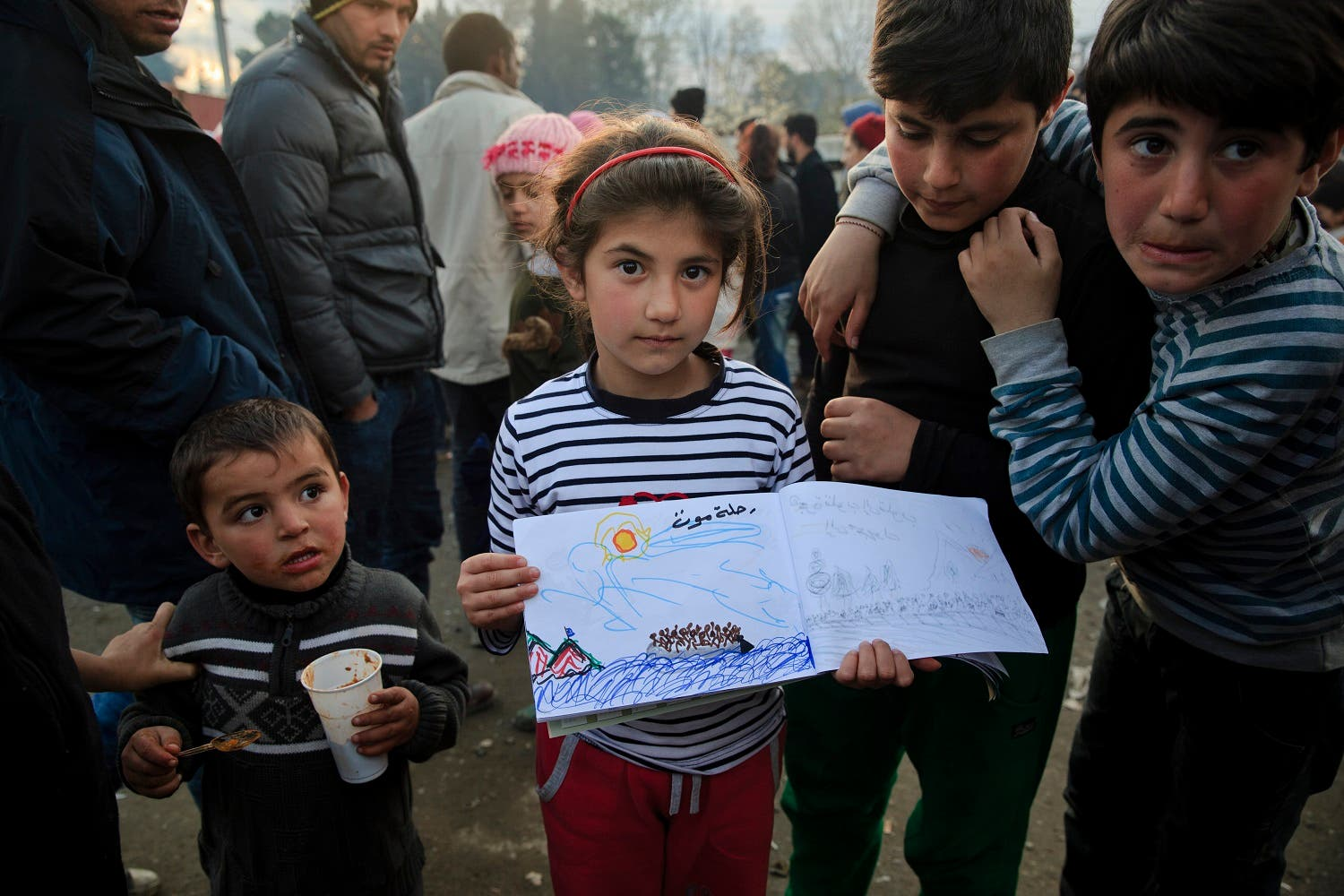 Shaharzad Hassan, 8 year-old from the Syrian city of Aleppo poses with a drawing she made at the northern Greek border station of Idomeni, Friday, March 11, 2016. At an overcrowded refugee camp on the Greek-Macedonian border, 8-year-old Shaharzad Hassan draws pictures of the harrowing events in her life over the past 18 months: Pictures of death in her home town of Aleppo, Syria, and her perilous journey to Europe. The title, of this drawing seen top right reads