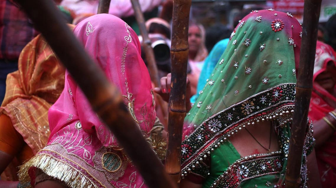 Indian Hindu women from Barsana with wooden sticks wait to beat the shield of men from Nandgaon during the Lathmar Holi festival (Photo: AP)