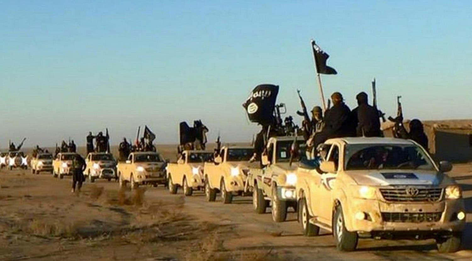 In this undated file photo released online in the summer of 2014 on a militant social media account, which has been verified and is consistent with other AP reporting, militants of the Islamic State group hold up their weapons and wave its flags on their vehicles in a convoy on a road leading to Iraq, in Raqqa, Syria. (Militant photo via AP, File)