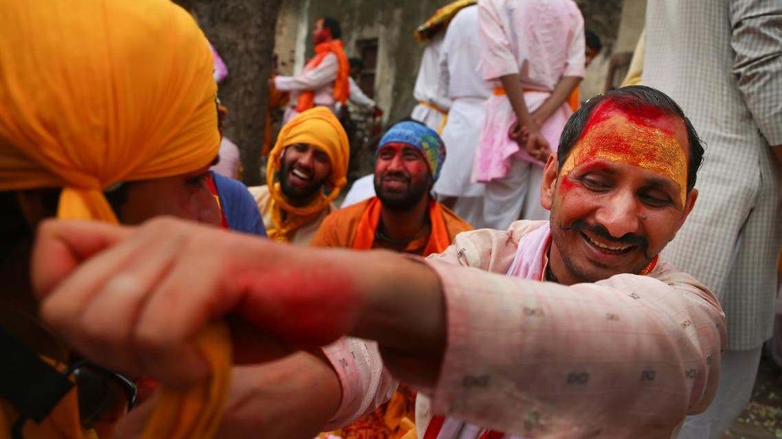 Smeared with colors villagers of Nandgaon get ready for the Lathmar Holi procession (Photo: AP)
