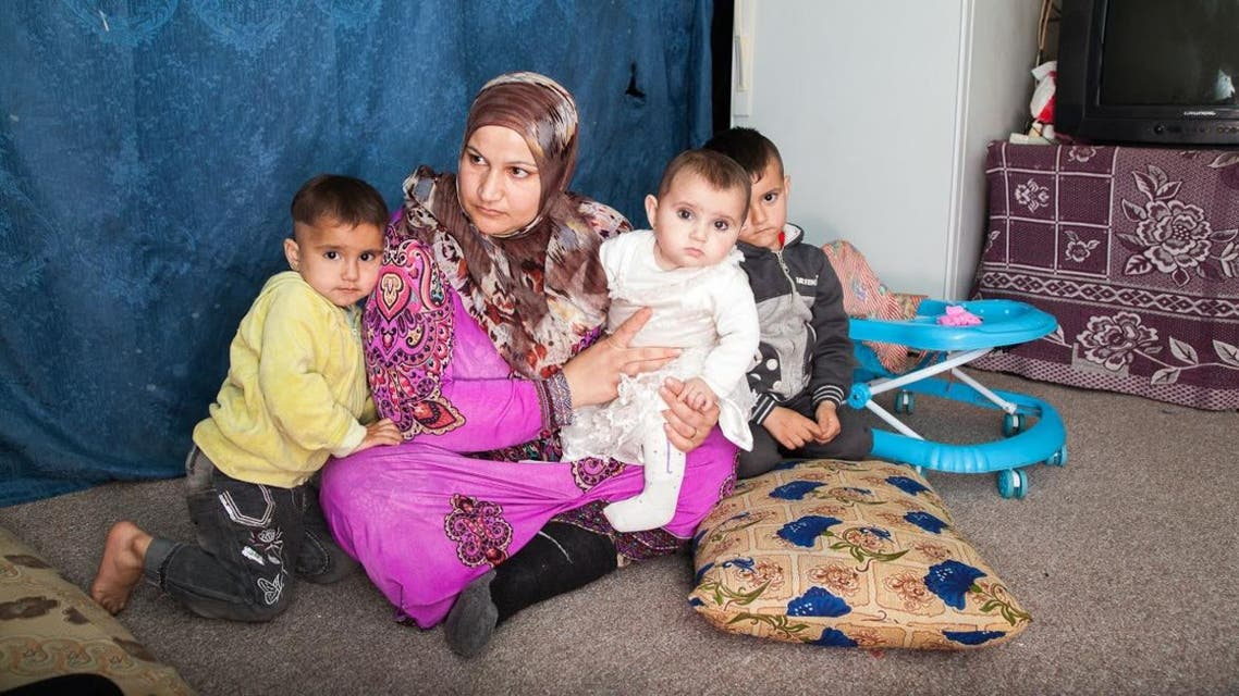 Dawlat sitting with her two daughters and one of her sons in her one room home in south Lebanon. (James Haines-Young)