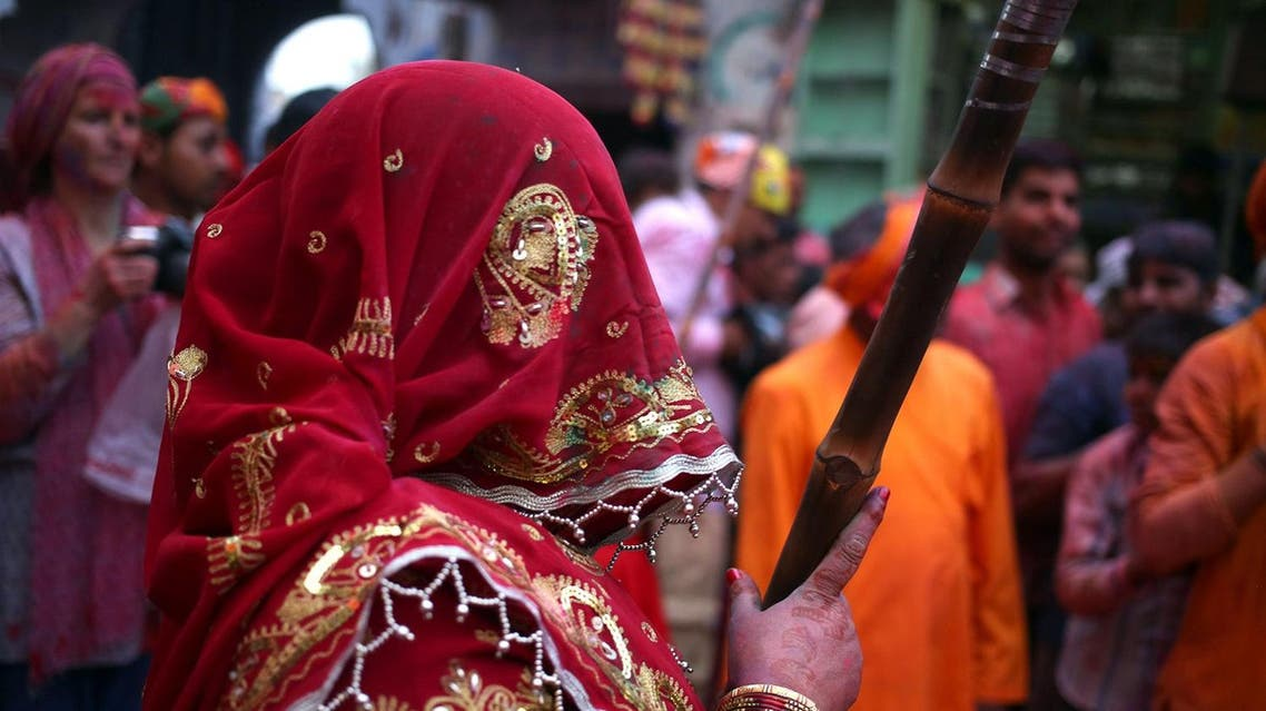 An Indian Hindu woman from Barsana gets ready to beat the shield of men from Nandgaon during the Lathmar Holi festival  (Photo: AP)
