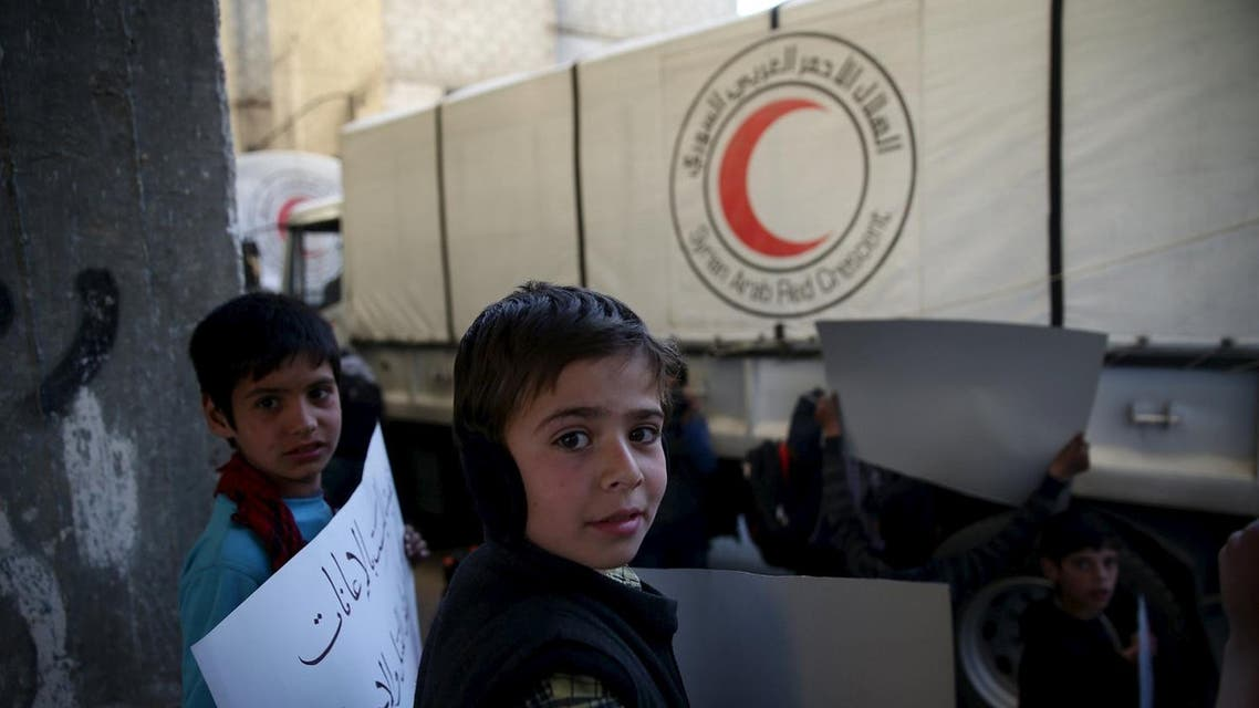 Children carry placards during an anti-government demonstration near a Red Crescent aid convoy in the rebel held besieged town of Jesreen, in the eastern Damascus suburb of Ghouta, Syria March 7, 2016. REUTERS