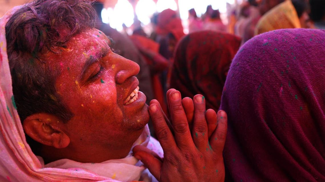 A Hindu devotees smeared with colors prays at the Radha temple before the procession for the Lathmar Holi festival (Photo: AP)