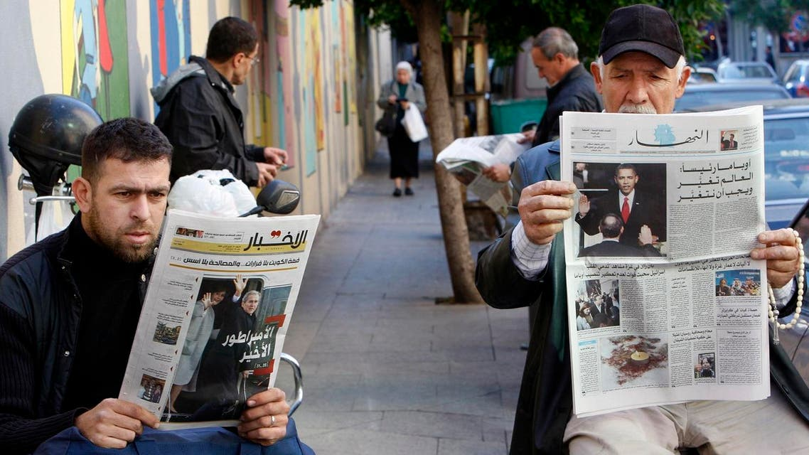 """Lebanese men, read newspapers with front pages pictures showing the inauguration ceremony of U.S. President Barack Obama, right, and in the left newspaper front page shows former President Bush and his wife boarding a helicopter and waving with Arabic headline read:""""The last emperor,"""" in Beirut, Lebanon, on Wednesday Jan. 21, 2009. (AP)"""