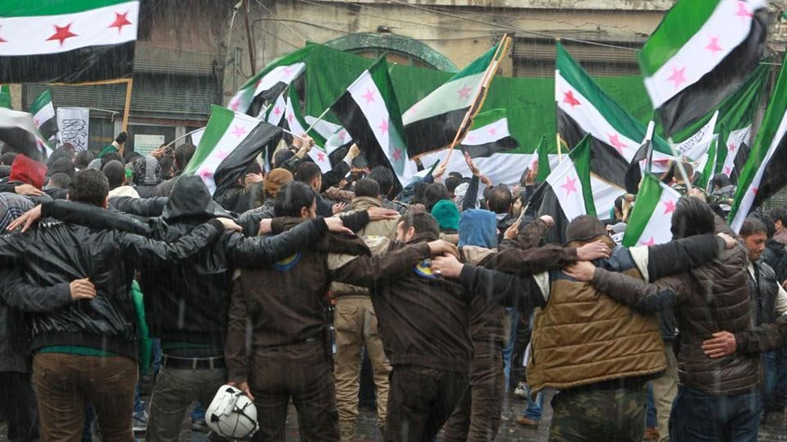 Civil defense members, rebel fighters and civilians carry opposition flags as they take part in a protest marking the fifth anniversary of the Syrian crisis in the old city of Aleppo, Syria March 15, 2016. (Reuters)