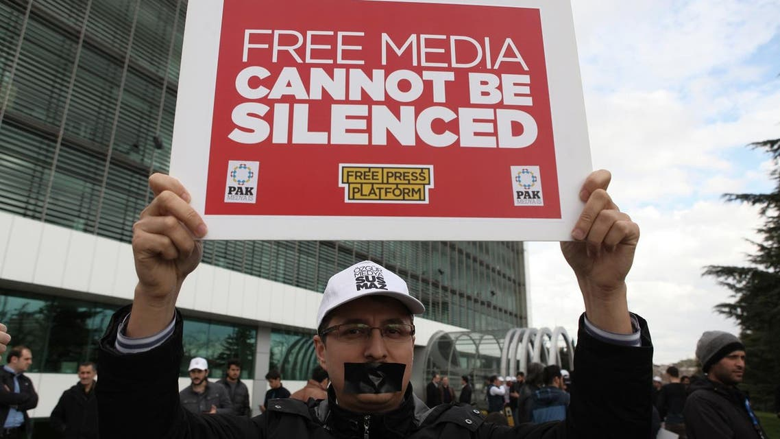 A man holds up a placard as he gathers in solidarity outside Zaman newspaper in Istanbul, Friday, March 4, 2016 after a local court ordered that Turkey's largest-circulation, opposition newspaper, which is linked to a U.S.-based Muslim cleric, be placed under the management of trustees _ a move that heightens concerns over deteriorating press freedoms in Turkey. The move against Zaman newspaper comes as the government has intensified a campaign against the movement led by Fethullah Gulen which it accuses of attempting to topple it.(AP)