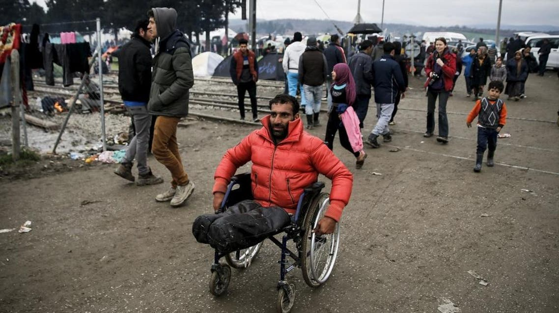 Syrian refugee Radwan Sheikho, 30, makes his way in a makeshift camp for refugees and migrants at the Greek-Macedonian border near the village of Idomeni, Greece, March 16, 2016 (Reuters)