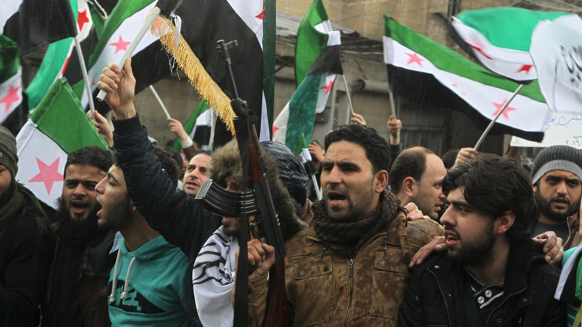 Rebel fighters and civilians carry opposition flags and chant slogans during a protest marking the fifth anniversary of the Syrian crisis in the old city of Aleppo, Syria March 15, 2016. reuters