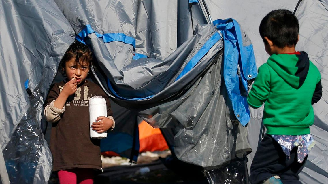 A migrant girl eats in a makeshift refugee camp at the northern Greek border point of Idomeni, Greece, Saturday, March 19, 2016. (AP)