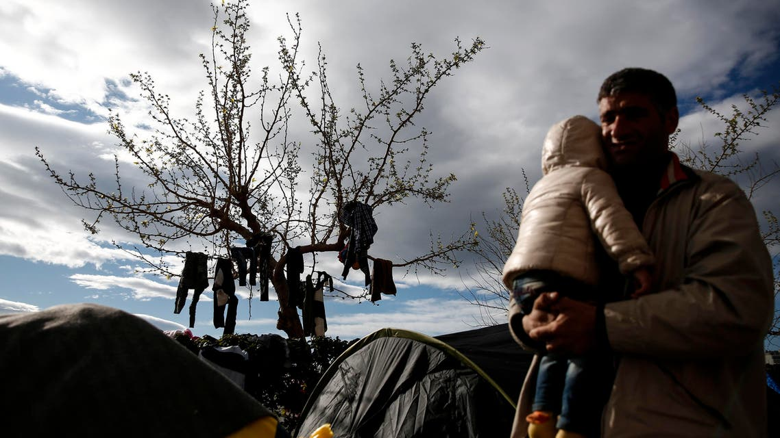 A man carrying a child walks in front of a tree with clothes drying on it at the Athens' port of Piraeus, on Saturday, March 19, 2016.  AP