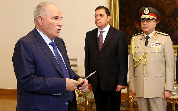 Ahmed el-Zend (left) being sworn in as justice minister last year Photo: Reuters