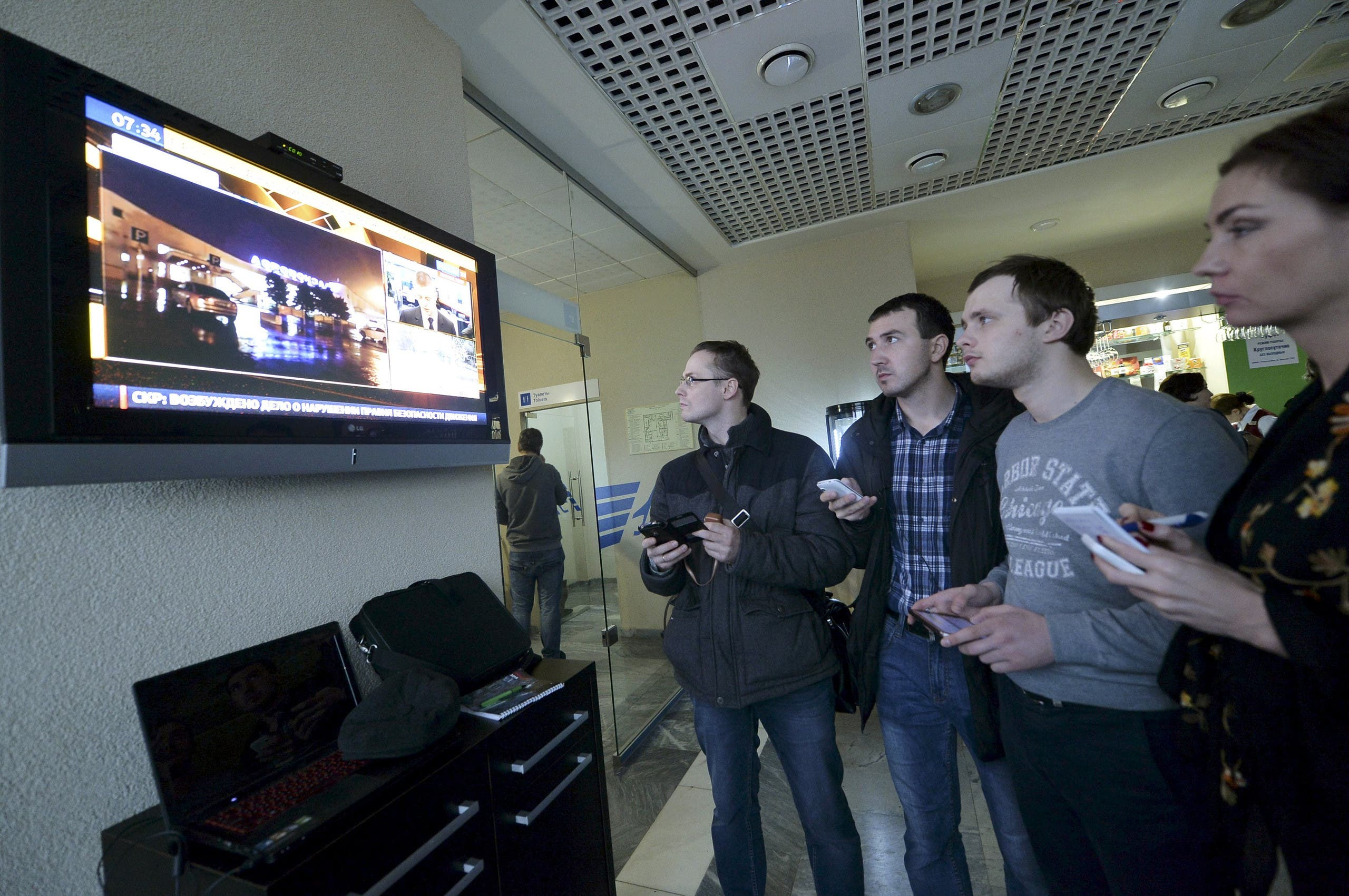 Journalists watch news on crashed Flydubai Boeing 737-800 at airport of Rostov-On-Don