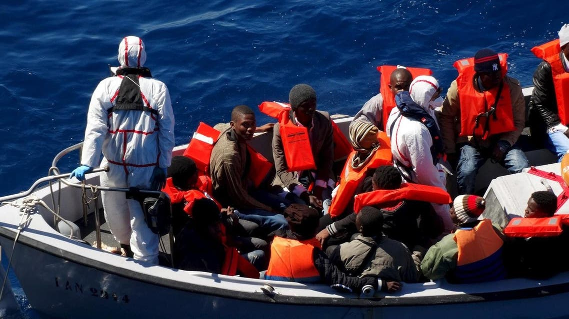 Migrants sit on a rescue boat during a rescue operation of migrants by Italian Navy vessels in this March 18, 2016 handout picture provided by Marina Militare. (Reuters/Marina Militare)