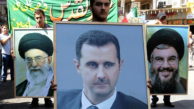 Pro-Syrian protesters carry posters of Assad, Nasrallah and Iran's Ayatollah Khamenei (Photo: Reuters)