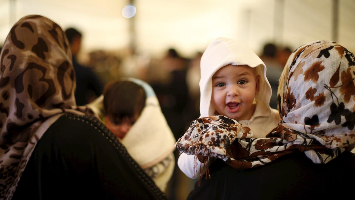 Syrian refugee mothers carry their babies during a ceremony at Al Zaatari refugee camp in the Jordanian city of Mafraq, near the border with Syria, March 1, 2016. (Reuters)