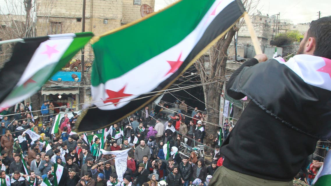 Protesters wave opposition flags as they take part in a protest marking the fifth anniversary of the Syrian crisis in the old city of Aleppo, Syria March 15, 2016.