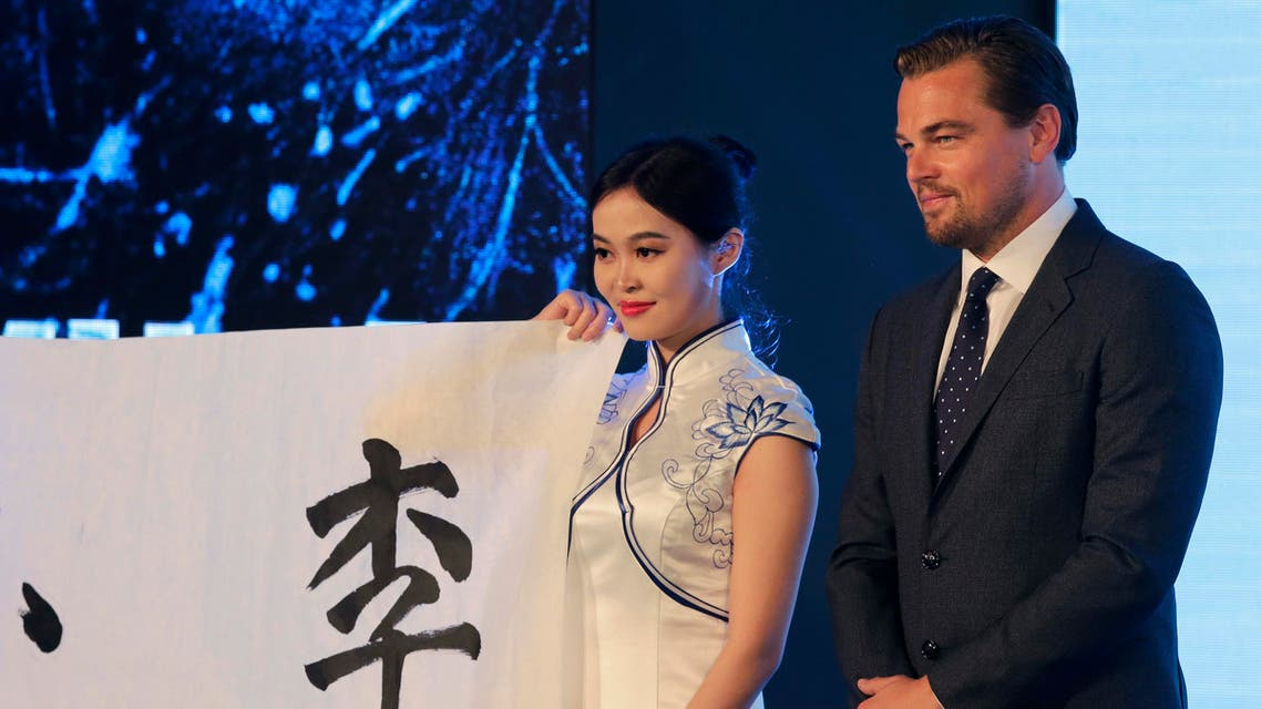 """Actor Leonardo DiCaprio, right, stands next to a hostess holding a paper bearing the Chinese characters which wrote by him during a news conference of the movie """"The Revenant"""" at a hotel in Beijing, Sunday, March 20, 2016. DiCaprio has praised China's work to combat climate change and says he believes the world's largest emitter of greenhouse gases could be """"the hero of the environmental movement."""" (AP Photo/Andy Wong)"""