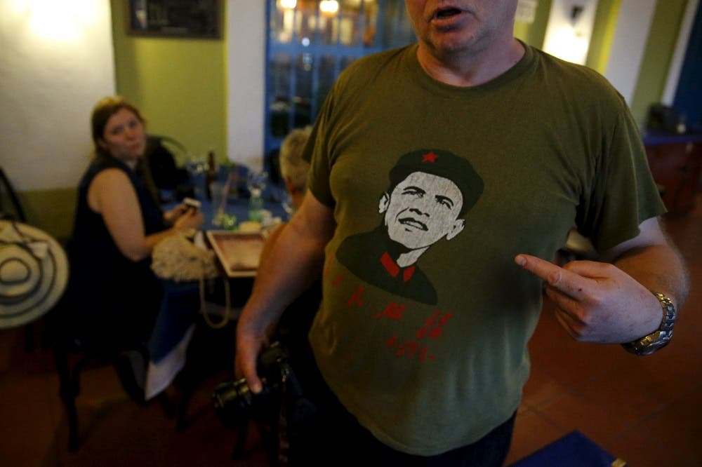A Norwegian tourist wears a shirt with a likeness of U.S. President Barack Obama in Vieja Havana as Obama takes part in a walking tour nearby, in Havana, Cuba. (Reuters)