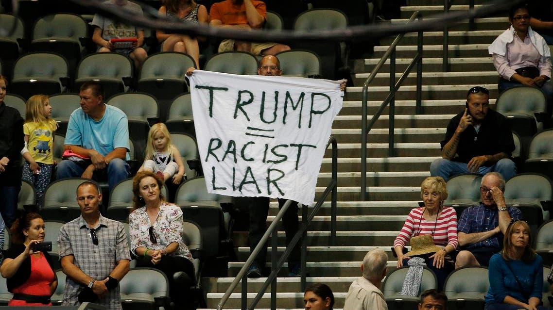 An anti-Donald Trump protester stands alone in the audience as the Republican presidential candidate speaks during a campaign rally Saturday, March 19, 2016, in Tucson, Ariz. (AP Photo/Ross D. Franklin)