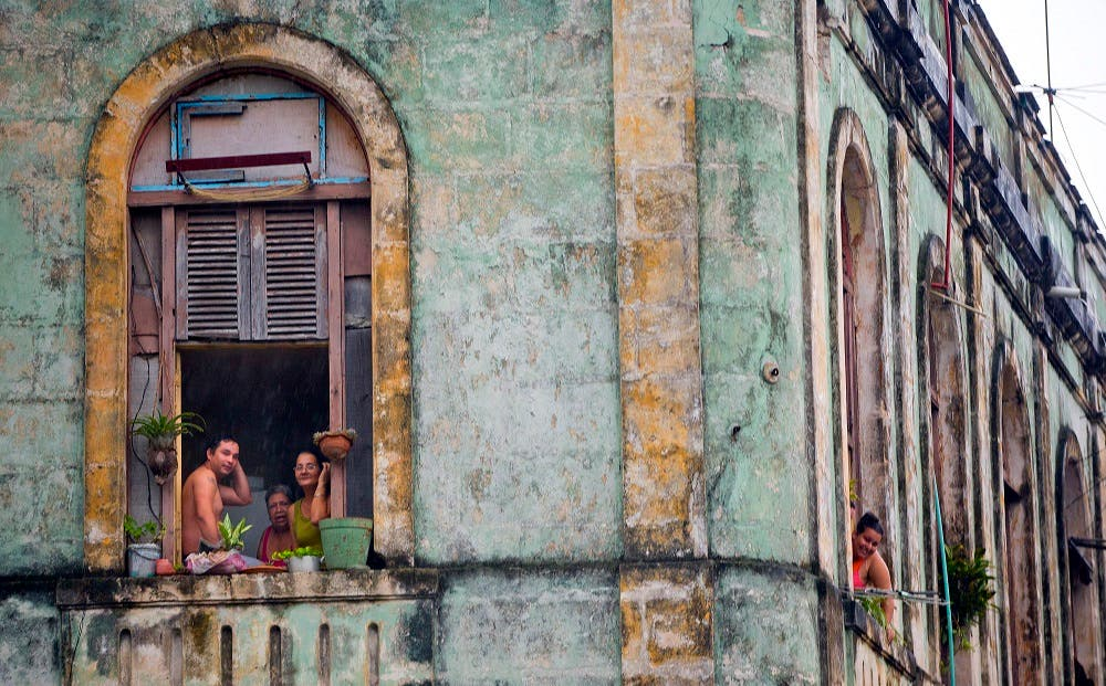Local Cubans watch from their homes as the motorcade of then-US President Barack Obama arrives in a section of Old Havana. (File photo: AP)