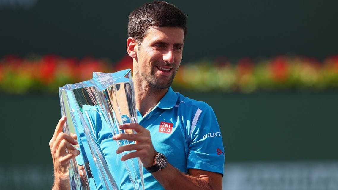 Novak Djokovic of Serbia holds up the winners trophy after his win over Milos Raonic of Canada. (AFP)
