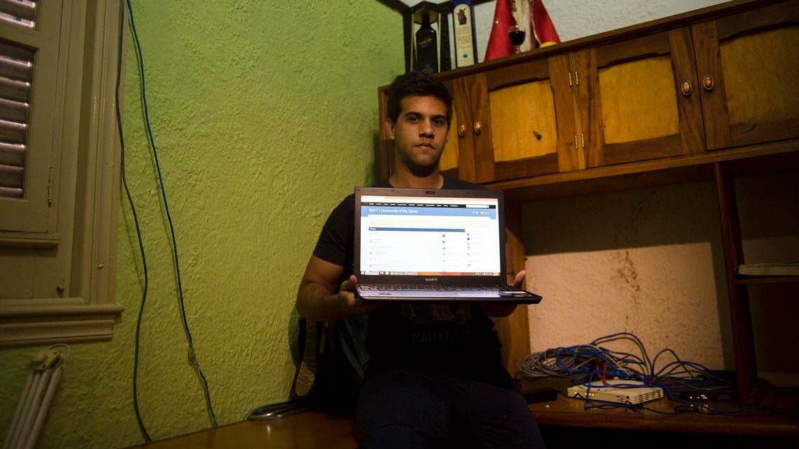 In this Jan. 4, 2015 photo, Rafael Antonio Broche Moreno poses with his computer, modem and intranet network cabling at his home in Havana. (AP)