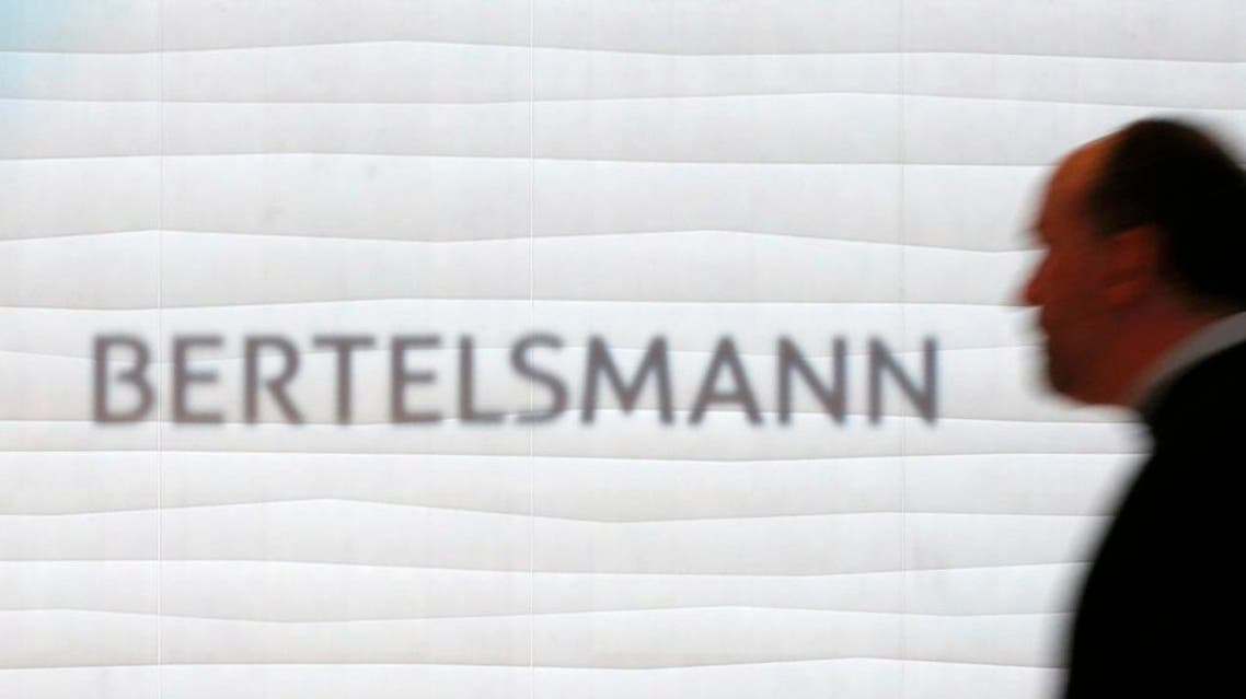 A man is silhouetted in front of the logo of German media group Bertelsmann prior to the annual news conference in Berlin, Germany, March 22, 2016 (Reuters)