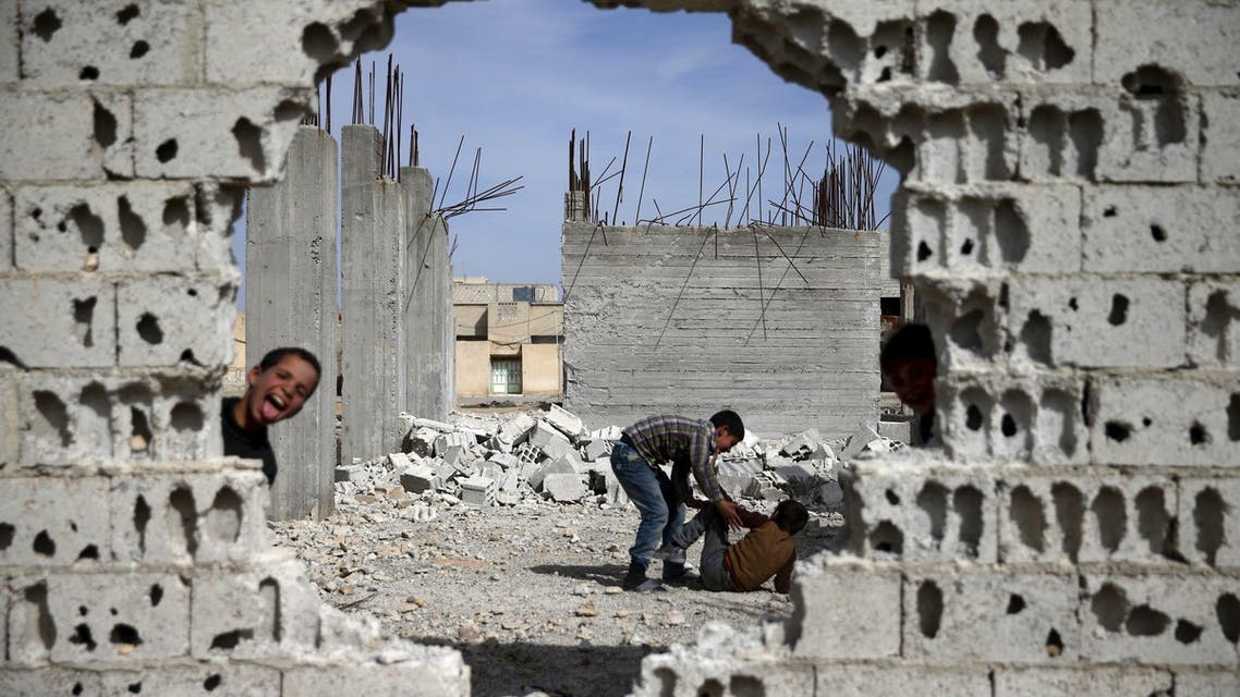 Boys play near rubble of damaged buildings in the rebel held besieged town of Douma, eastern Damascus suburb of Ghouta, Syria March 19, 2016. (Reuters)