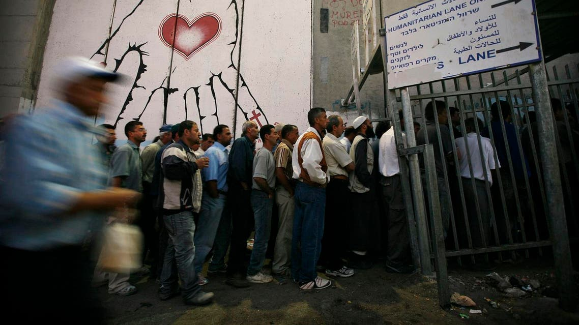 Palestinian workers wait to cross a checkpoint to work in Israel at the separation barrier in the West Bank town of Bethlehem, early Tuesday, June 16, 2009. (AP)