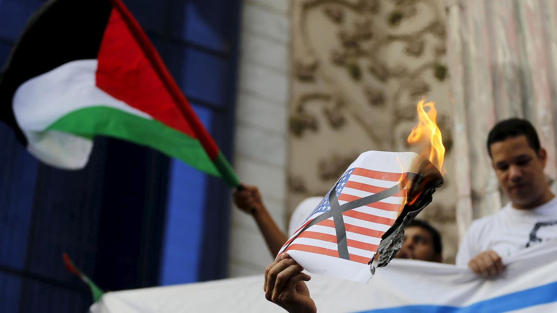An activist shouts slogans against the U.S with a burning picture of their flag during a protest in front of the Syndicate of Journalists in Cairo, August 2, 2015, to condemn Friday's arson attack by Israel in the West Bank.  (Reuters)