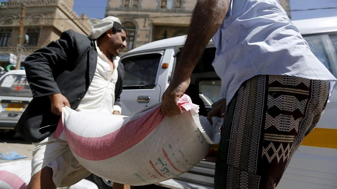 People carry a sack of wheat to a van outside a food distribution center for poor families in Yemen capital Sanaa in this March 17, 2016  (Reuters)