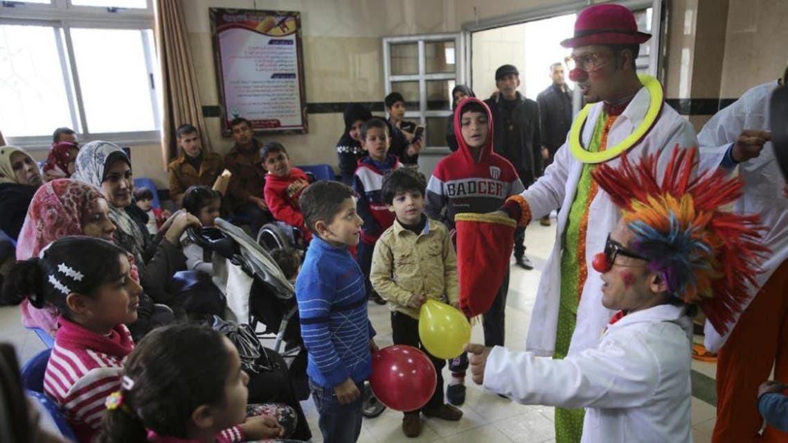 In this Thursday, March 17, 2016 photo, Palestinian clown doctors 24-year-old Majed Kaloub, top right, and 33-year-old Alaa Miqdad, right, perform for children during their visit at the waiting room at Al-Rantisi children's hospital in Gaza City (AP)