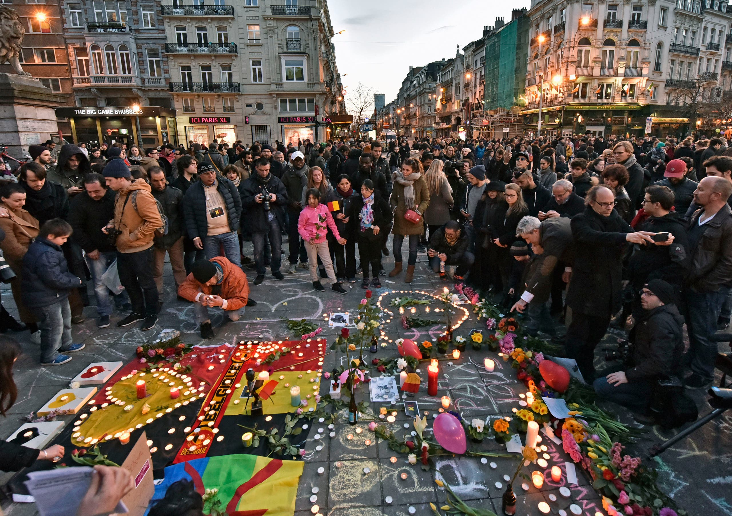 People bring flowers and candles to mourn at the Place de la Bourse in the center of Brussels, Tuesday, March 22, 2016. (AP)