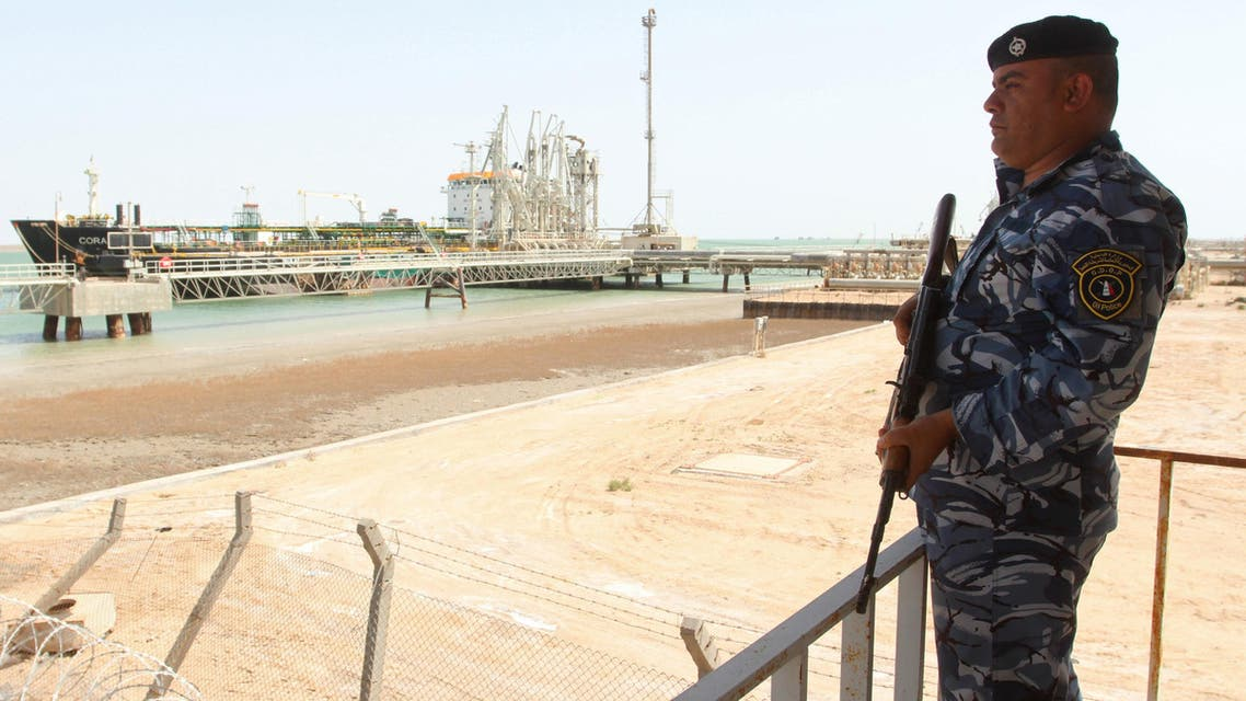 A member of the Iraqi security force stands guard near a gas carrier as it prepares to set sail at the southern port of Khor al-Zubair in Basra province, March 20, 2016. (Reuters)