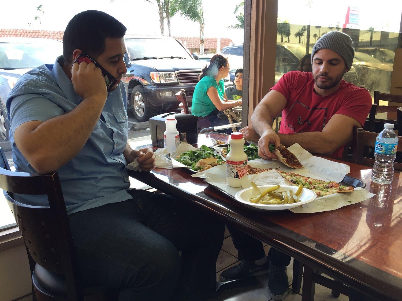 Nas Juma, 22, left, and Omar Ghanim, 23, enjoy Lebanese pizza at Forn Al Hara restaurant in Orange County's Little Arabia in Anaheim, Calif., Tuesday, March 22, 2016. (AP)