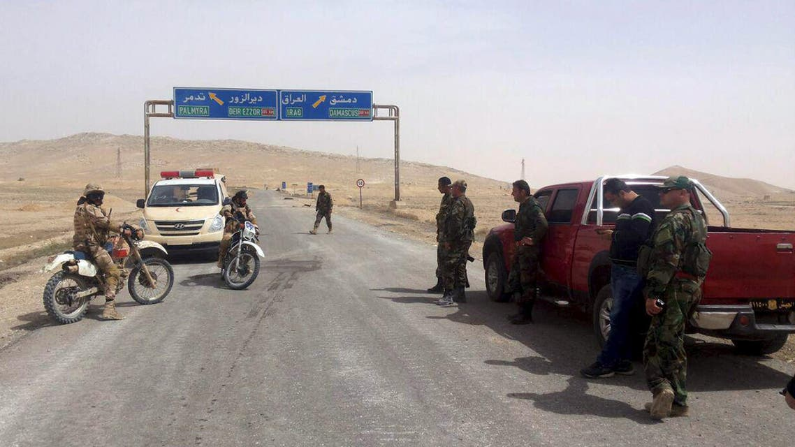 Forces loyal to Syria's President Bashar al-Assad stand near a road sign that shows the direction to the historic city of Palmyra in this picture provided by SANA on March 24, 2016.  (Reuters)