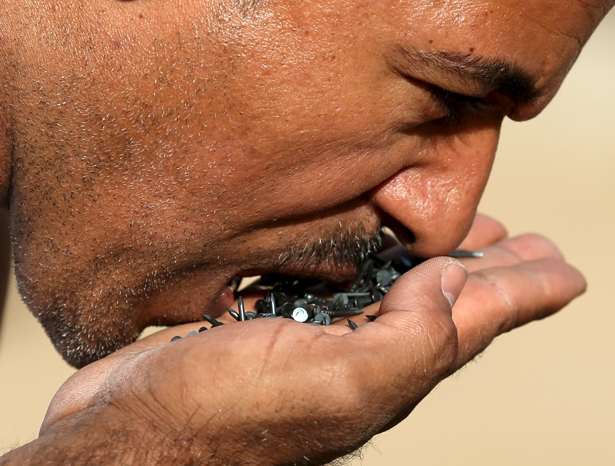 Egyptian strongman Karim Hussein, 38, eats nails in Cairo, Egypt, March 18, 2016. (Reuters)