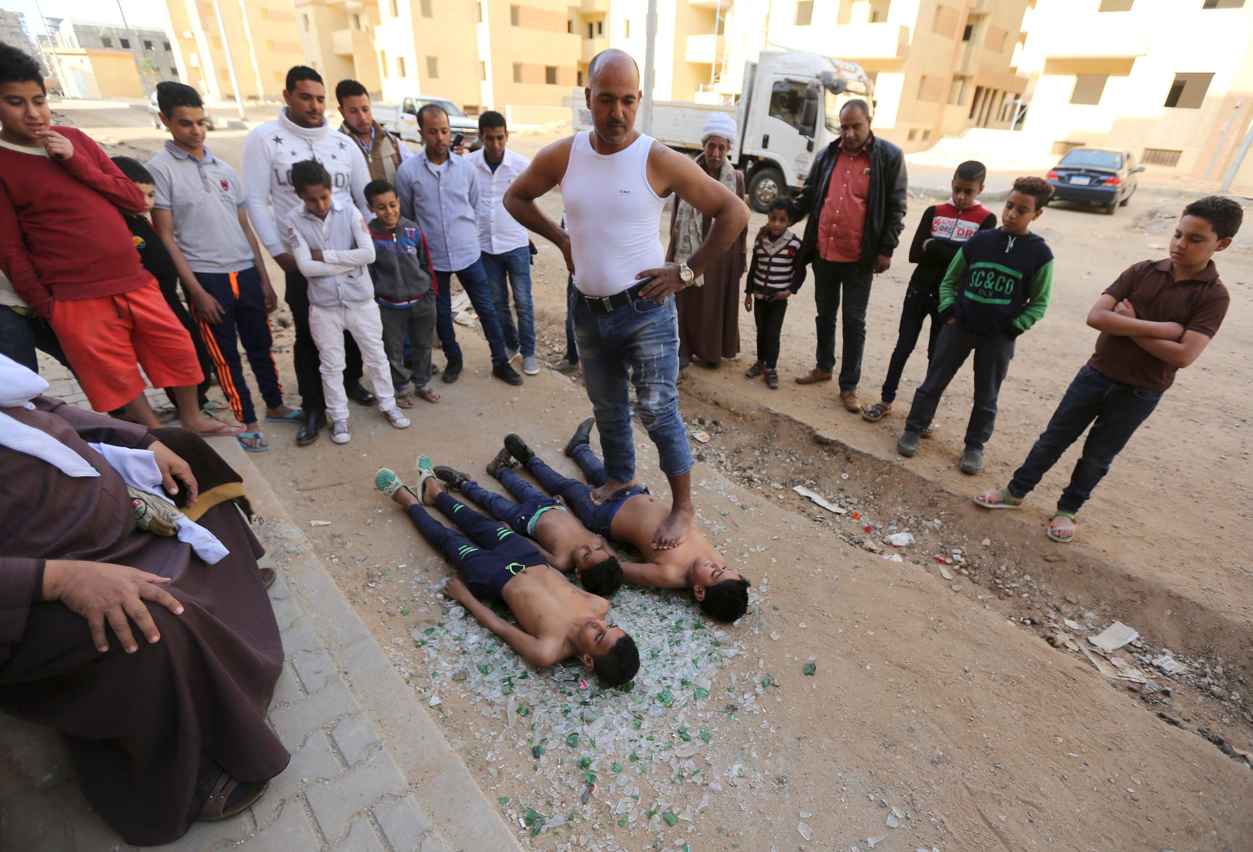 Egyptian strongman Karim Hussein, 38, walks over his sons as they sleep on broken glass in Cairo, Egypt, March 18, 2016. (Reuters)