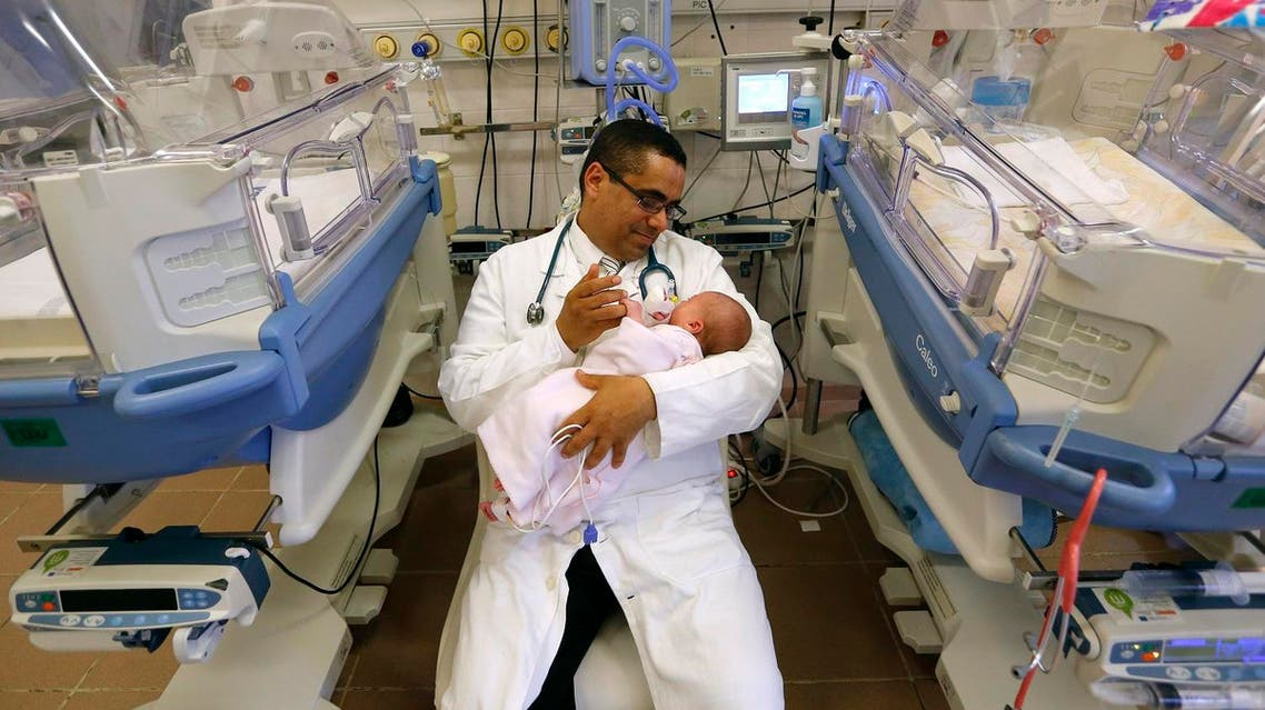 """Abdulrahman Abdulrab, a Yemeni-born Hungarian doctor who was voted """"Doctor of the Year"""" by Hungarian patients, holds a new born baby at the hospital in Gyula. (Reuters)"""