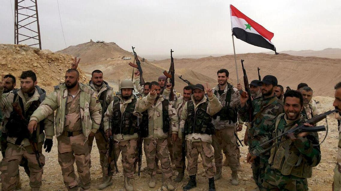 Forces loyal to Syria's President Bashar al-Assad flash victory signs and carry a Syrian national flag on the edge of the historic city of Palmyra in Homs Governorate, in this handout picture provided by SANA on March 26, 2016. (Reuters)