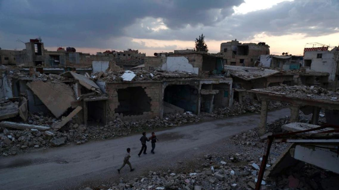 Syrian children walk past heavily damaged buildings in the rebel-held town of Douma, on the eastern edges of the capital Damascus on February 27, 2016, on the first day of the landmark ceasefire agreement (AFP)