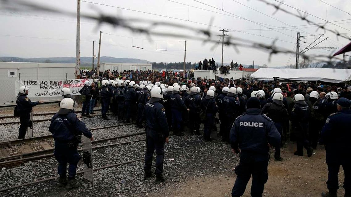 Greek police stand guard in front of migrants and refugees during a protest at a makeshift camp at the Greek-Macedonian border near the village of Idomeni, Greece, March 27, 2016 (Reuters)