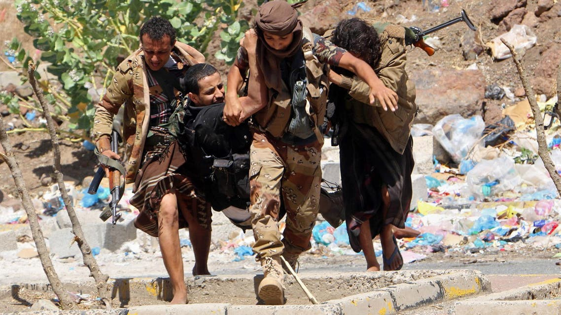 Fighters from local resistance units carry a fellow fighter who was injured in clashes between local fighters and Houthis in March 2016 (AP)