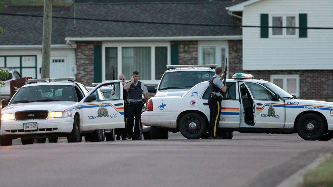 Royal Canadian Mounted Police officers take cover behind their vehicles in Moncton, New Brunswick, on Wednesday, June 4, 2014. AP