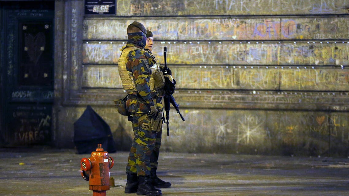 Belgian soldiers patrol, as people pay tribute to the victims of Tuesday's bomb attacks, at the Place de la Bourse in Brussels, Belgium, March 26, 2016. (Reuters)