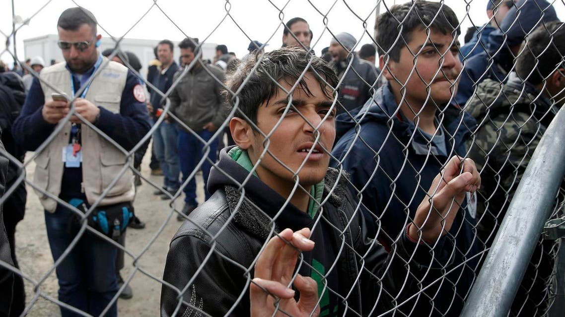 Migrants and refugees stand by a fence at a makeshift camp at the Greek-Macedonian border near the village of Idomeni, Greece, March 27, 2016. (Reuters)