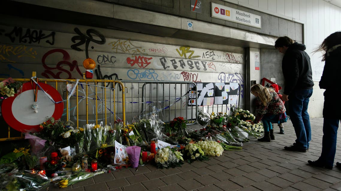 People stop and look at floral tributes placed outside the Maelbeek metro station, the scene of one of the bomb attacks on the Belgian capital, in Brussels, Saturday, March 26, 2016. (AP)