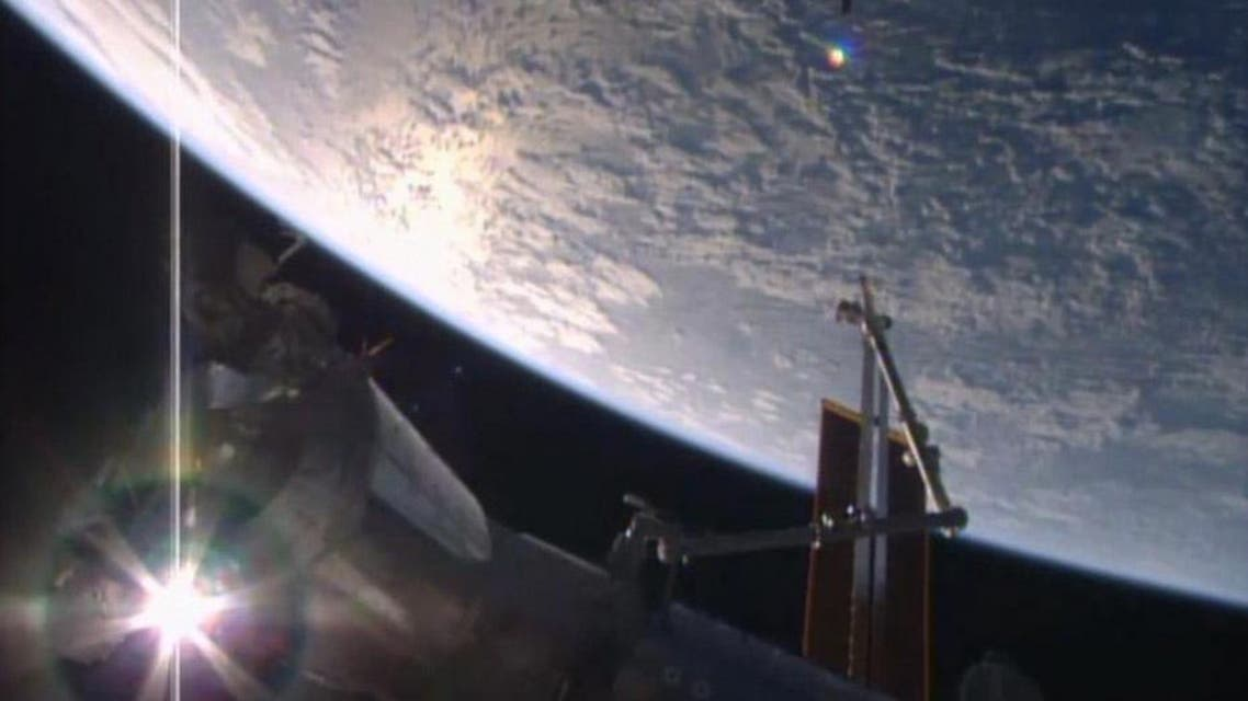 In this image made from video provided by NASA, Orbital ATK's Cygnus cargo ship, top, approaches the International Space Station on Saturday, March 26, 2016. The cargo carrier was launched from Cape Canaveral on Tuesday. (NASA via AP)